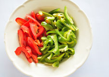 Red and green sliced pepper on a plate. Photo red and green sliced pepper on a plate. To prepare and cook it bright white background. As fried foods Stock Photography