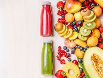 Red and green smoothies and juices beverages in bottles with various fresh organic fruits and berries ingredients on white wooden. Background, top view. Healthy royalty free stock photography