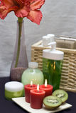 Red and green spa. Spa elements in red, green and white colors. Candles and kiwis focused royalty free stock photo