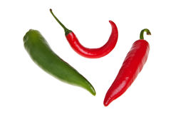 Red and green spicy peppers. Red and green spicy peppers isolated over white background Royalty Free Stock Images
