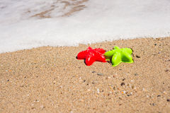 Red and green starfish-shaped molds on the sand Stock Photo