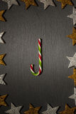 Red green striped candy cane on dark slate background Stock Image