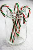 Candy Canes In A Jar. Red and green striped candy canes in a glass jar on a white textured surface royalty free stock photography