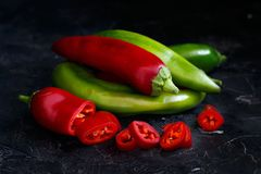 Red and green sweet peppers. On dark background Stock Image