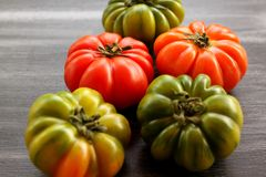 Red and green tomatoes on black table, high angle view Royalty Free Stock Images