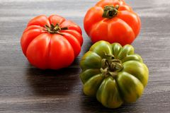 Red and green tomatoes on black table, high angle view Stock Photo
