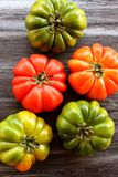 Red and green tomatoes on black table, top view, flat lay Stock Photos