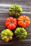 Red and green tomatoes on black table, top view, flat lay Royalty Free Stock Photos