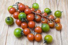Red and green tomatoes on branch. On a wooden table Royalty Free Stock Photo