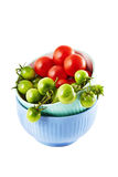 Red and green tomatoes in the dish on white background Stock Photo