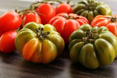Red and green tomatoes and few cherry tomatoes on black table, high angle view Royalty Free Stock Images