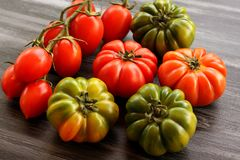 Red and green tomatoes and few cherry tomatoes on black table, high angle view Stock Photo