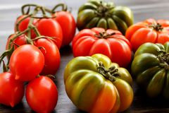 Red and green tomatoes and few cherry tomatoes on black table, high angle view Royalty Free Stock Photography