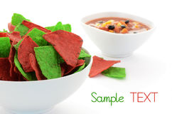 Red and green tortilla chips. Festive red and green tortilla chips with black bean and corn salsa for holiday snacking on white background with space for your Stock Photo
