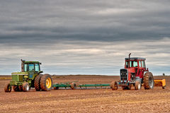Red and Green Tractors. Two tractors in a field that has just been prepaired for new crop of wheat Stock Photos