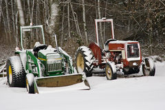 Red and green tractors dusted with snow. Red and green tractors dusted with new snow Royalty Free Stock Photography