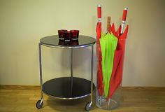 Red and green umbrellas in big glass vase near coffee table with three candle glasses. Home design. Office design. Sweden Royalty Free Stock Images