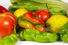 Red and green vegetables of different types. Different vegetables and fruis such as tomatoes, red and green peppers, lettuces and lemons Royalty Free Stock Photos
