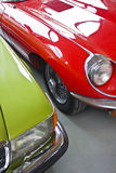 Red and green vintage cars. Old english car in red and old german car in green stock photo