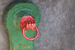 Red and green vintage knocker with hand, Ireland. This old metal knocker is a decorative feature of a water pump from the 1800's in Knightstown, Ireland Royalty Free Stock Images