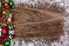 Red, green and white Christmas ornament side border on wood Royalty Free Stock Photography