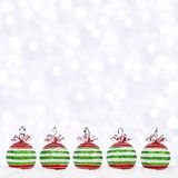 Red, green, white Christmas ornaments in snow with twinkling background Stock Image