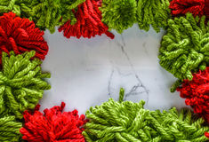 Red and green yarn on marble background. DIY concept. Red and green yarn frame a marble background. Pom Poms or puffs can be used as a Christmas background or royalty free stock photography