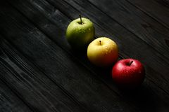 Red green yellow apples in a diagonal row with water drops on black wooden table, back light Royalty Free Stock Photography