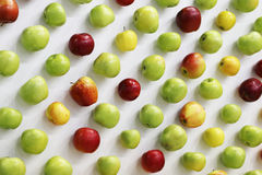 Red, green and yellow apples  on white desk Stock Images