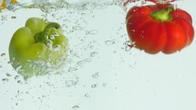 Red, green, yellow bell pepper falls to the water, causing bubbles and scattered water Royalty Free Stock Image