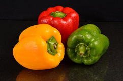 Red, Green and Yellow bell peppers. Fresh bell peppers on a wet black background Stock Photo