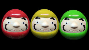 Red green yellow color daruma doll in black isolate background Royalty Free Stock Images