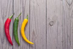 Red, green and yellow hot chili pepper on wooden planks. Royalty Free Stock Photography