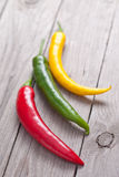 Red, green and yellow hot chili pepper on wooden planks. Stock Images