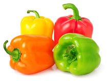 Red, green, yellow and orange bell peppers isolated Stock Images