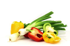 Red, green and yellow peppers and some green onion. Colorful display of red, green and yellow peppers and some green onions Royalty Free Stock Photos
