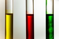 Red green yellow solution dilute in clear liquid in test tube. Close up royalty free stock images
