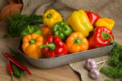 Red, green and yellow sweet bell peppers on table, Stock Photography