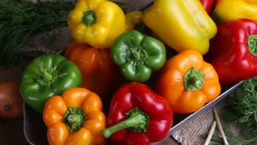 Red, green and yellow sweet peppers on a table in a jar in the form of pepper stock footage