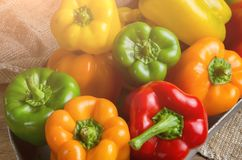 Red, green and yellow sweet bell peppers on table, Stock Images