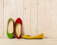 Red, green and yellow women`s shoes ballerinas on wooden backg Royalty Free Stock Images