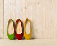Red, green and yellow women`s shoes ballerinas on wooden backg. Round. Selective focus stock photo