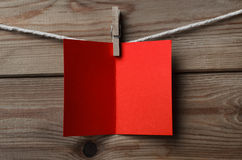 Red Greetings Card Pegged to String on Wood Background. An opened, blank red greeting or Christmas card, pegged on to string against wood plank background royalty free stock images