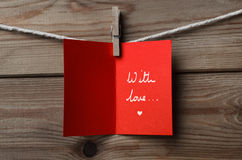 Red Greetings Card Pegged to String on Wood. A red greeting card, pegged on to string against wood plank background Opened to display handwritten words 'With stock image