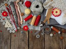 Red and grey accessories for needlework on wooden background. Knitting, embroidery, sewing. Small business. Income from hobby. Stock Photo