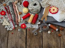 Red and grey accessories for needlework on wooden background. Knitting, embroidery, sewing. Small business. Income from hobby. Red and grey accessories for Royalty Free Stock Photography