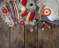 Red and grey accessories for needlework on wooden background. Knitting, embroidery, sewing. Small business. Income from hobby. Red and grey accessories for Stock Photos