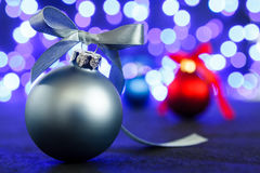Red, grey and blue christmas balls, blured purple lights at the background Royalty Free Stock Photo