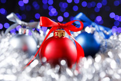 Red, grey and blue christmas balls, blured purple lights at the background Royalty Free Stock Images
