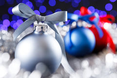 Red, grey and blue christmas balls, blured purple lights at the background Stock Photos